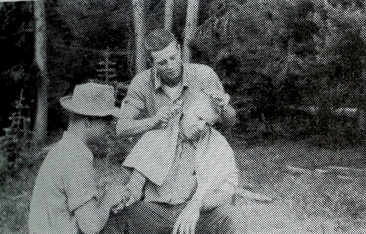 Two men cut another man's hair.
